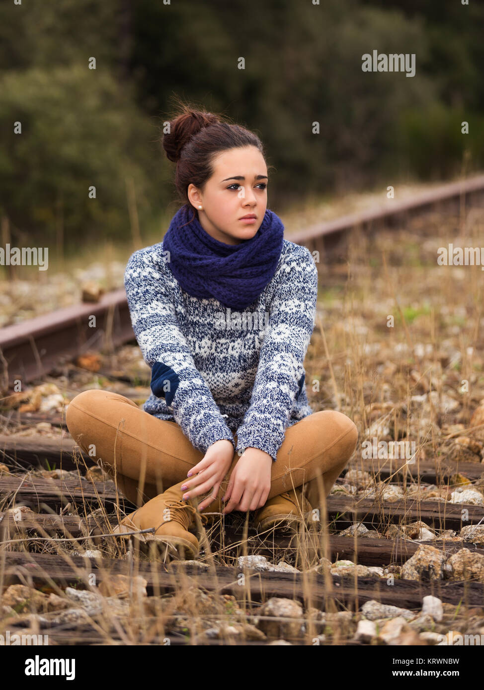 Young woman sitting on old railway - Stock Image