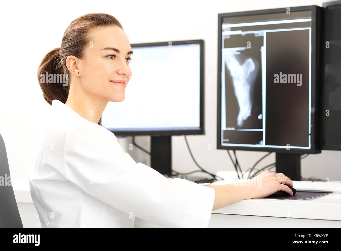 a doctor is sitting at a desk in a doctor's office and examining the medical records. - Stock Image