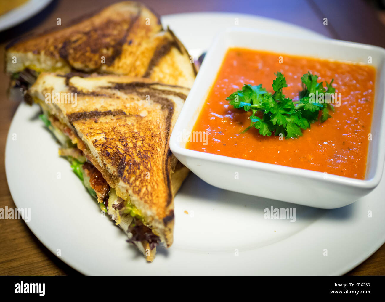 A BLT sandwich (bacon, lettuce, tomato sandwich) on marble rye bread and tomato soup from Culina Cafe in Edmonton, - Stock Image