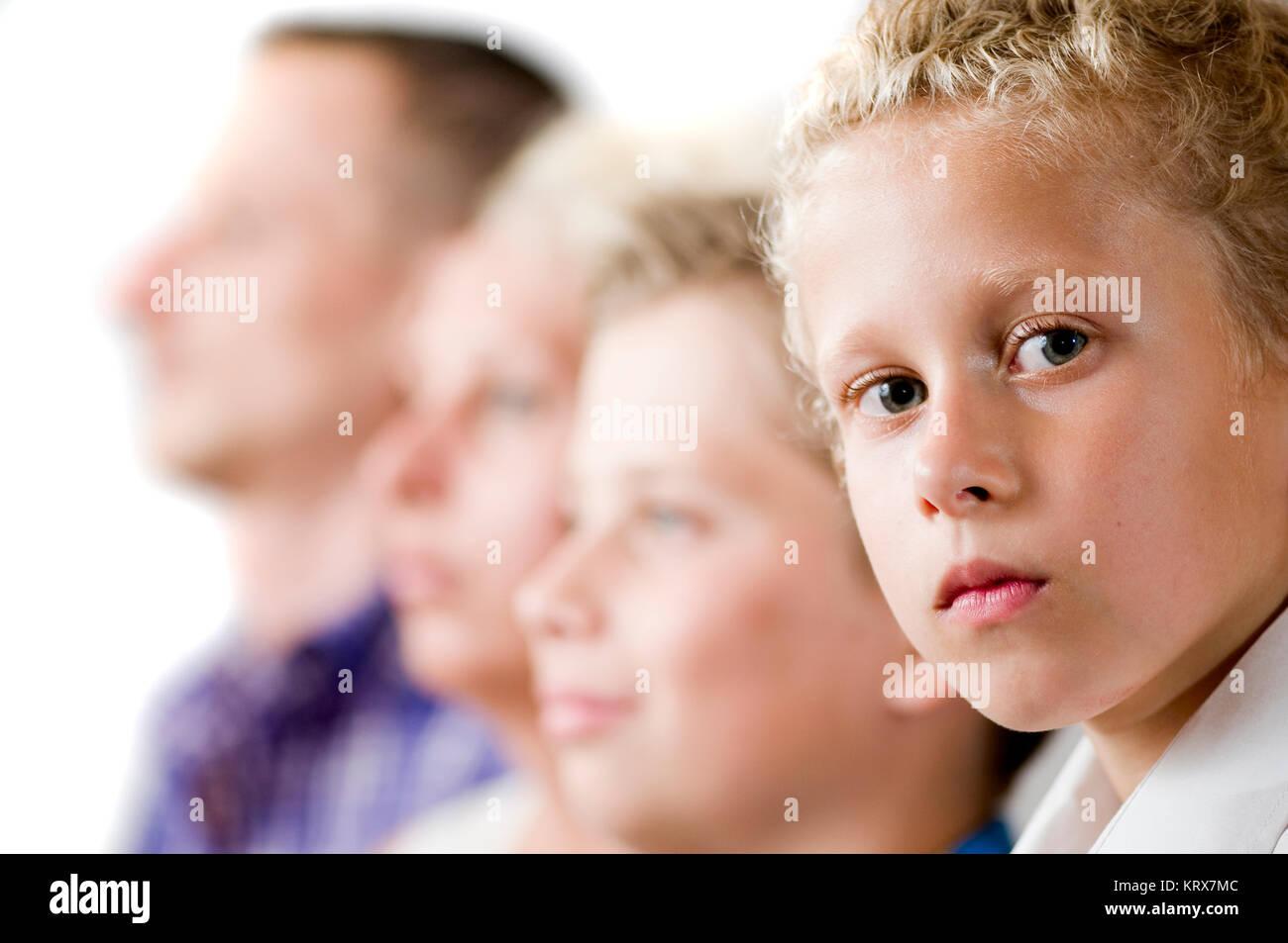 Seitenansicht einer Familie mit zwei halbwüchsigen Söhnen. Jüngster Sohn im Fokus blickt ernst in - Stock Image