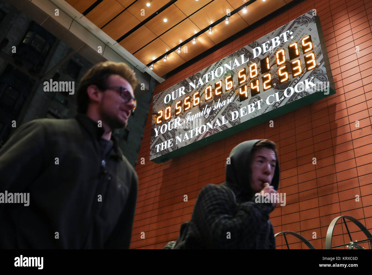 New York, USA. 20th Dec, 2017. People pass by the National Debt Clock in Manhattan of New York City, the United - Stock Image