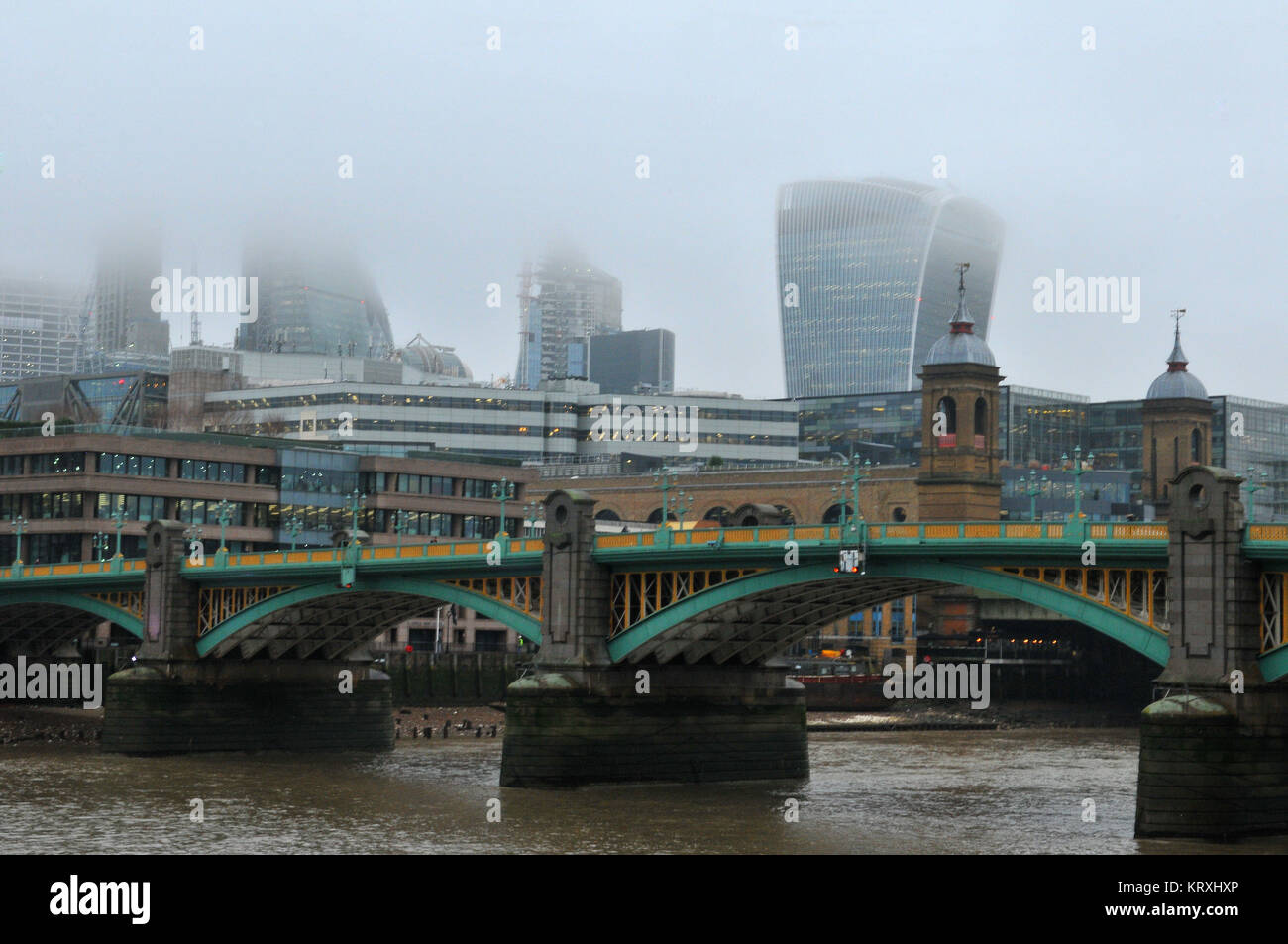 London, UK. 21st Dec, 2017. a misty or foggy morning over the river Thames with Southwark Bride and Cannon Street - Stock Image