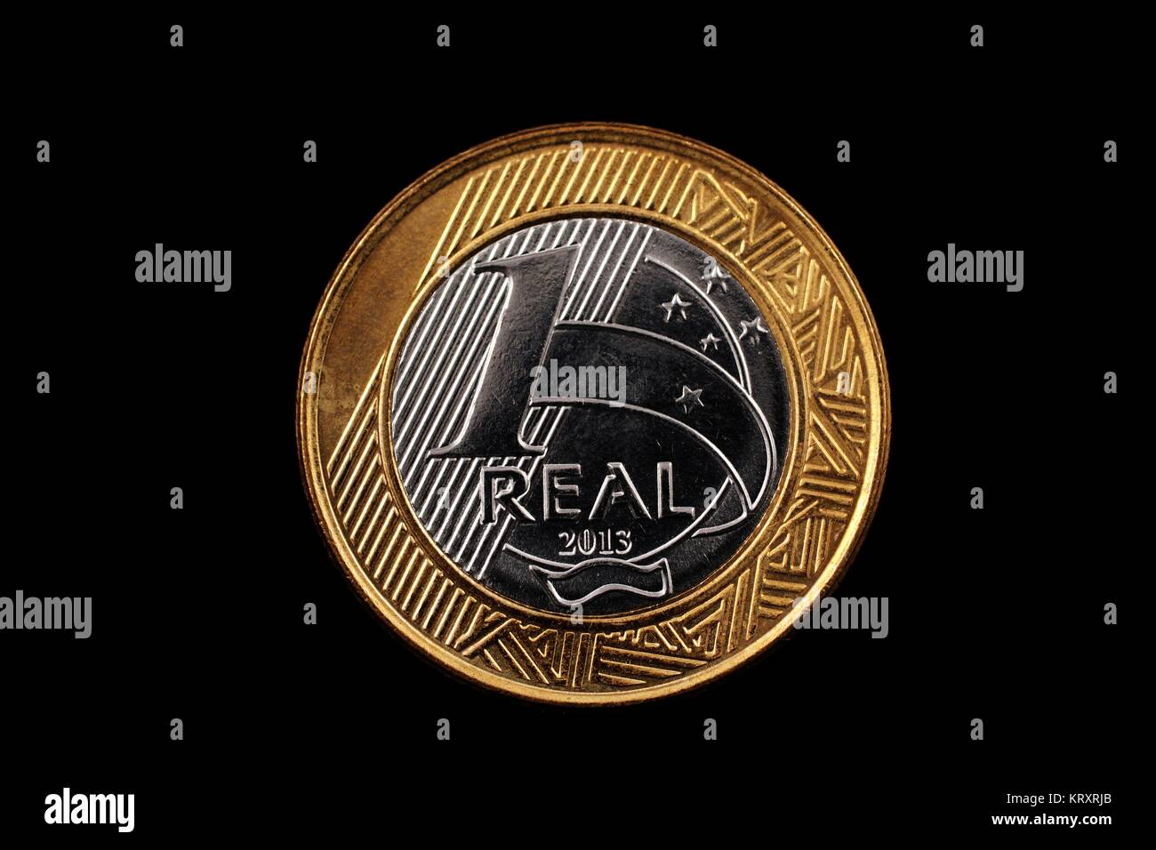 A super macro image of a bimetallic one real coin isolated on a black background - Stock Image