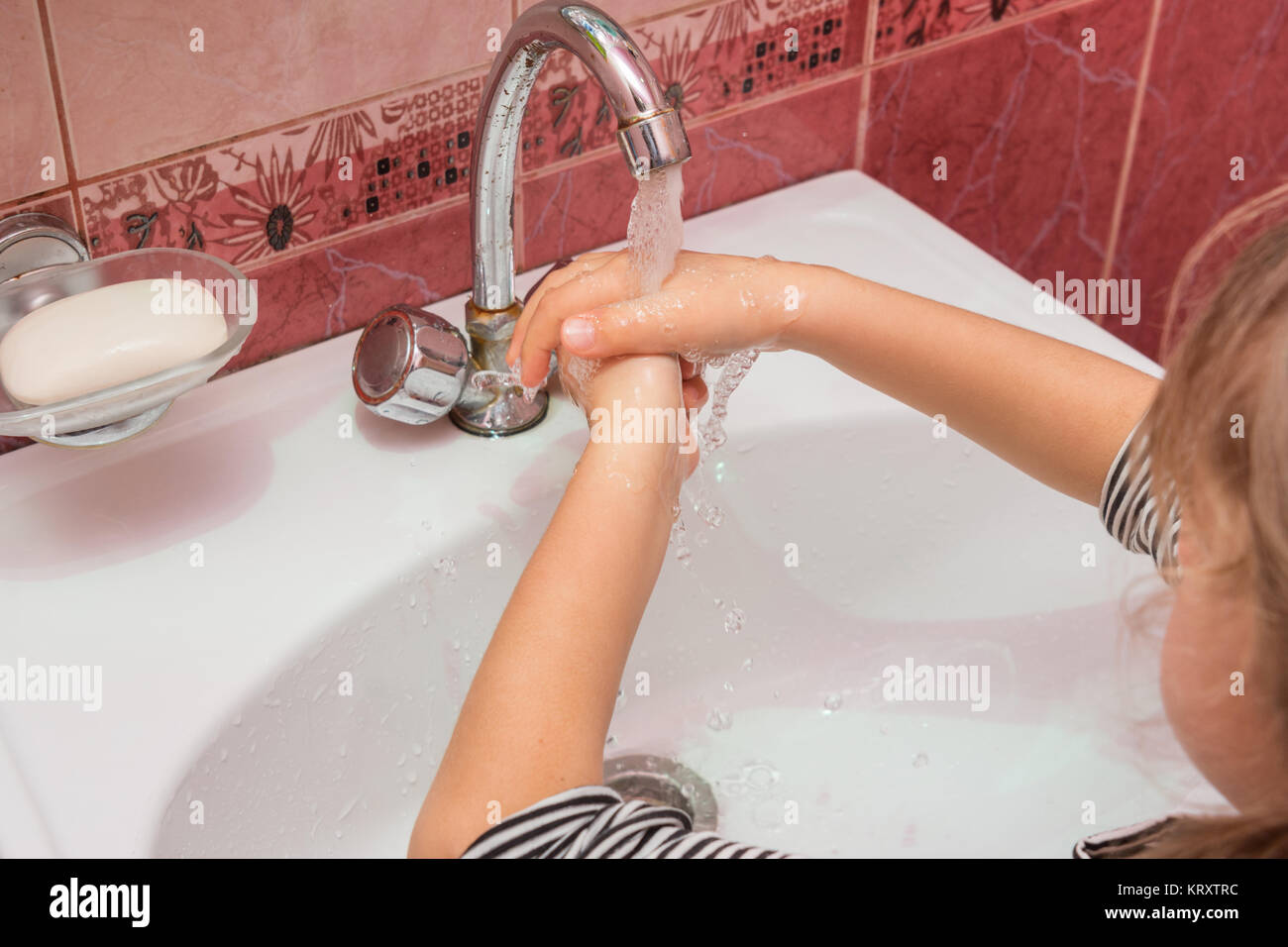 Five-year girl washes hands with soap - Stock Image