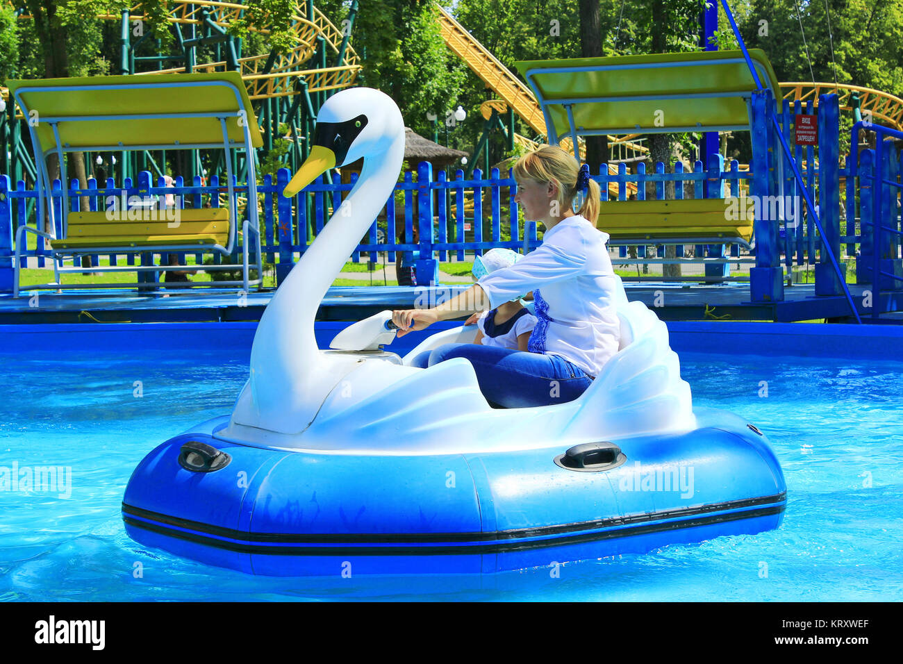 children and their parents ride water catamarans inflatable in Gorky park in Kharkiv - Stock Image