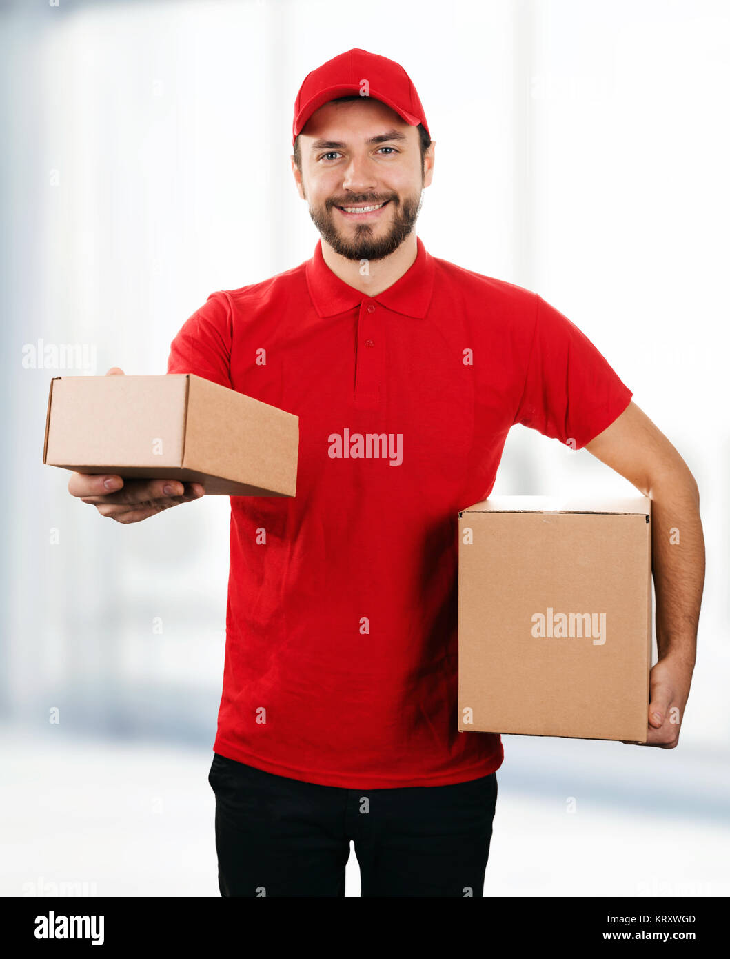 delivery service - young smiling deliveryman with cardboard boxes - Stock Image