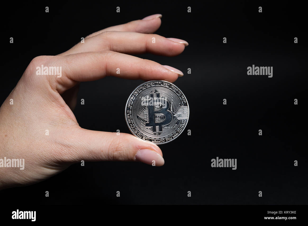 Woman hand holding a silver metal bitcoin on black background as virtual currency or e-commerce in cyberspace concept - Stock Image