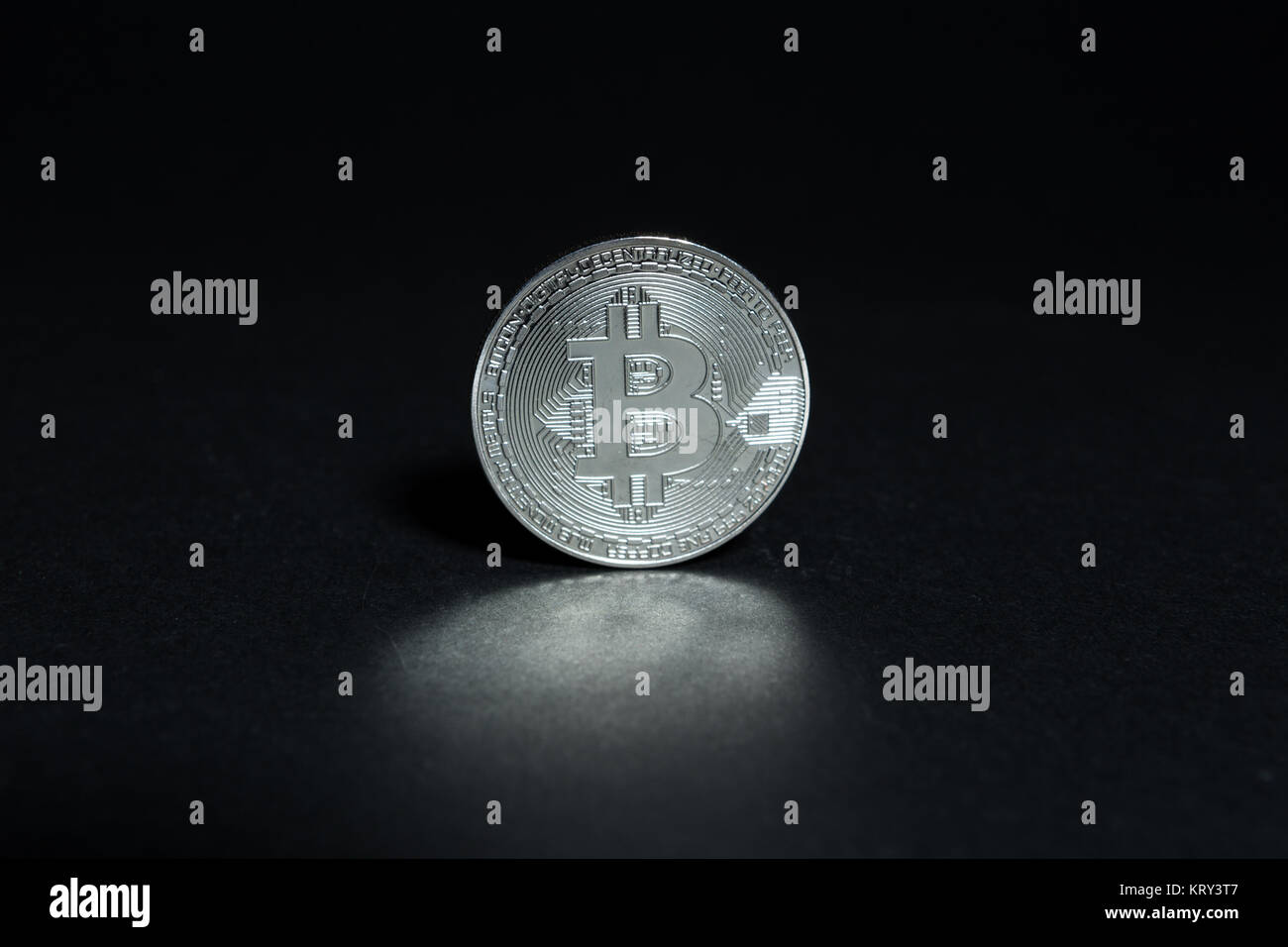 One single silver bitcoin on dark black background with copy text space area - Stock Image
