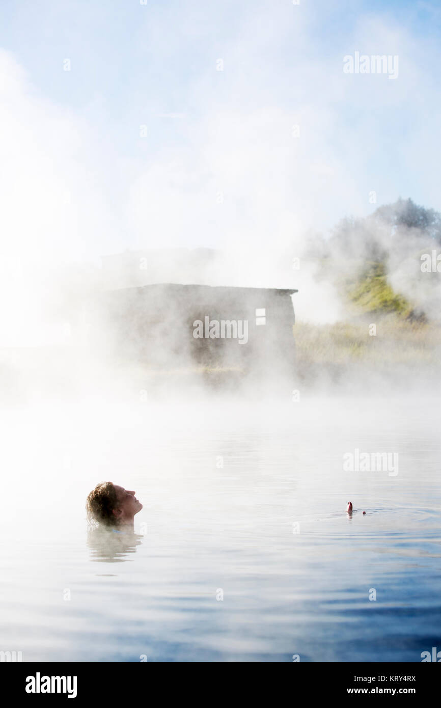 A woman bathing in The Secret Lagoon in Iceland - Stock Image