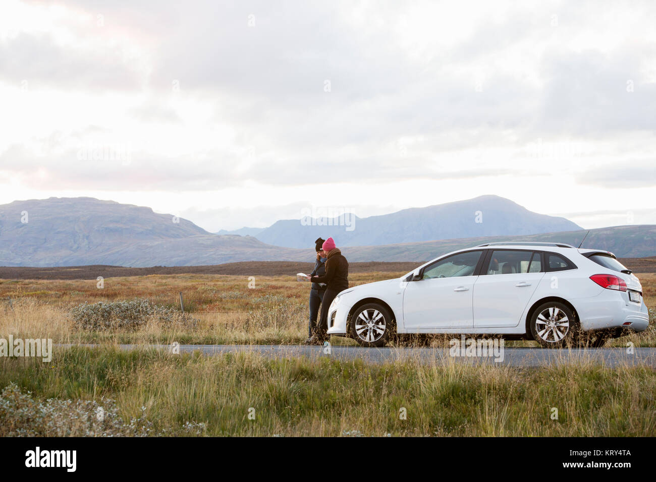 Two women and their car on the side of the road in Iceland - Stock Image