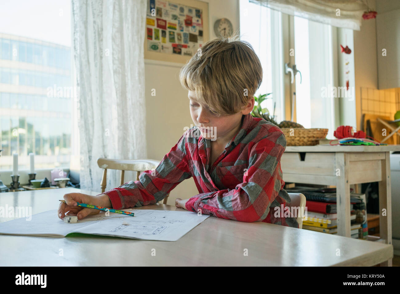 A young boy sitting at a table drawing - Stock Image