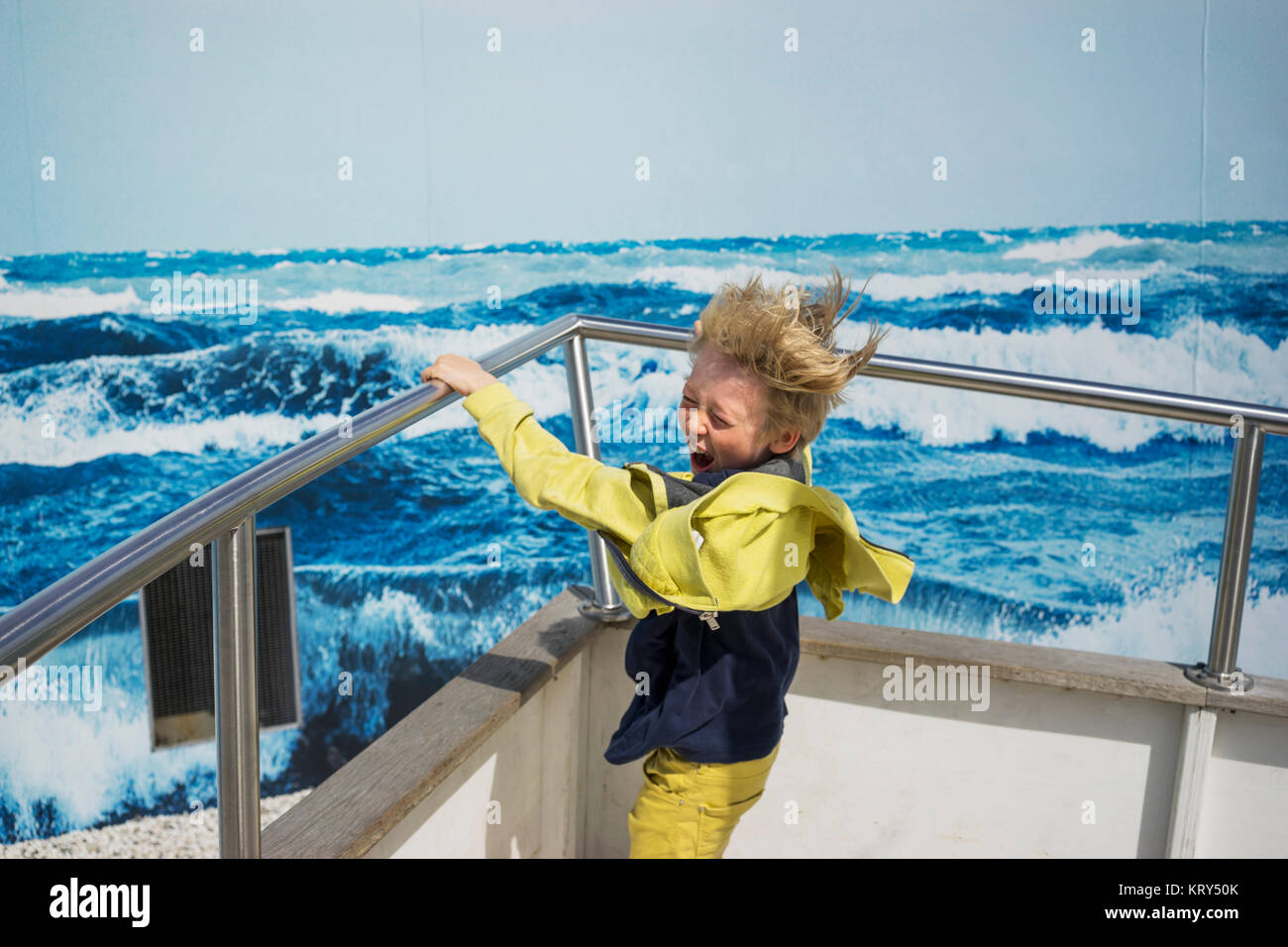 A young boy on a boat in wet weather gear - Stock Image