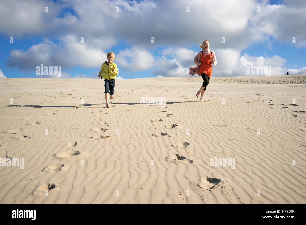Two children running along the beach - Stock Image