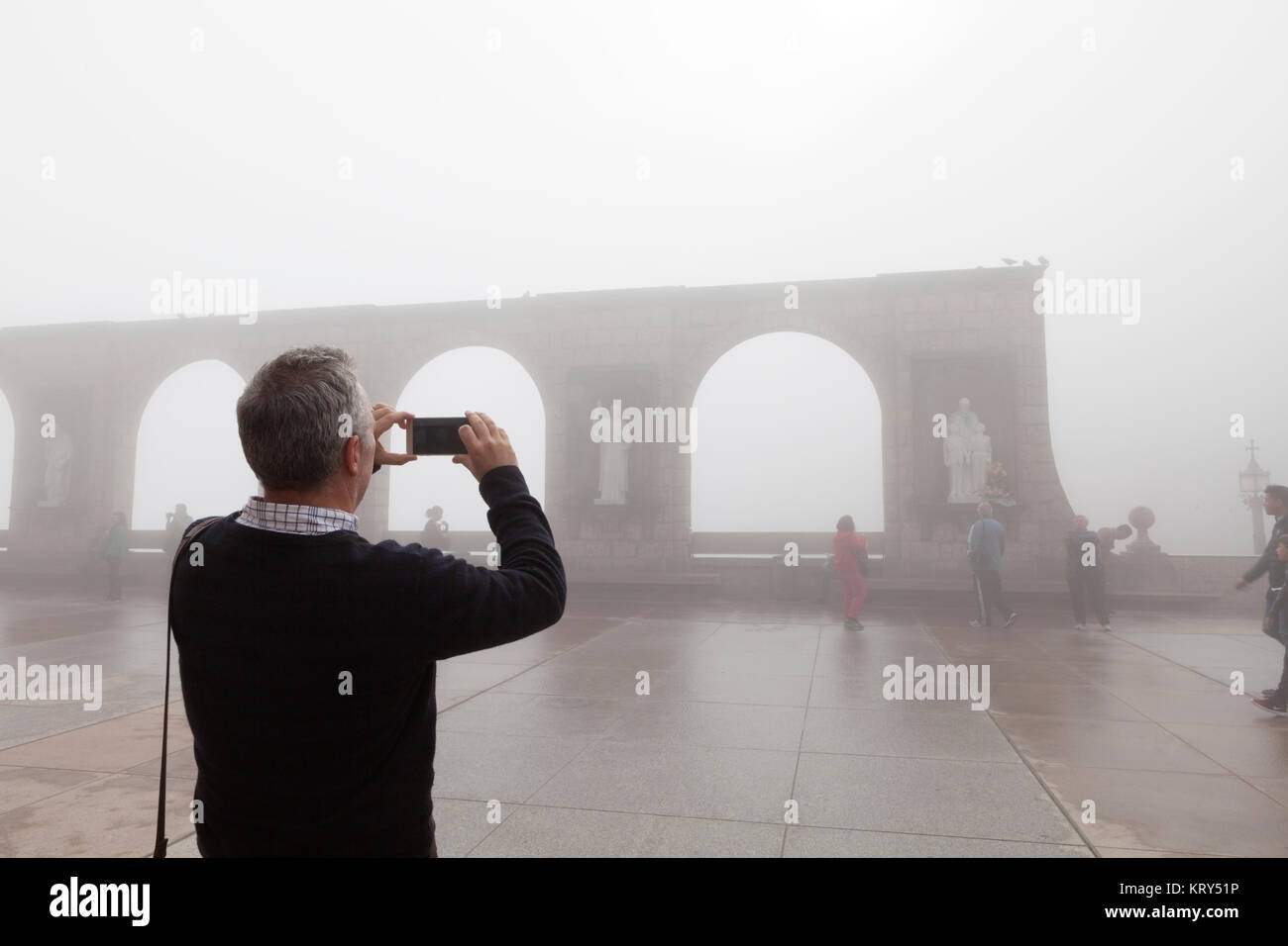 Man taking a photograph in mist in Barcelona - Stock Image