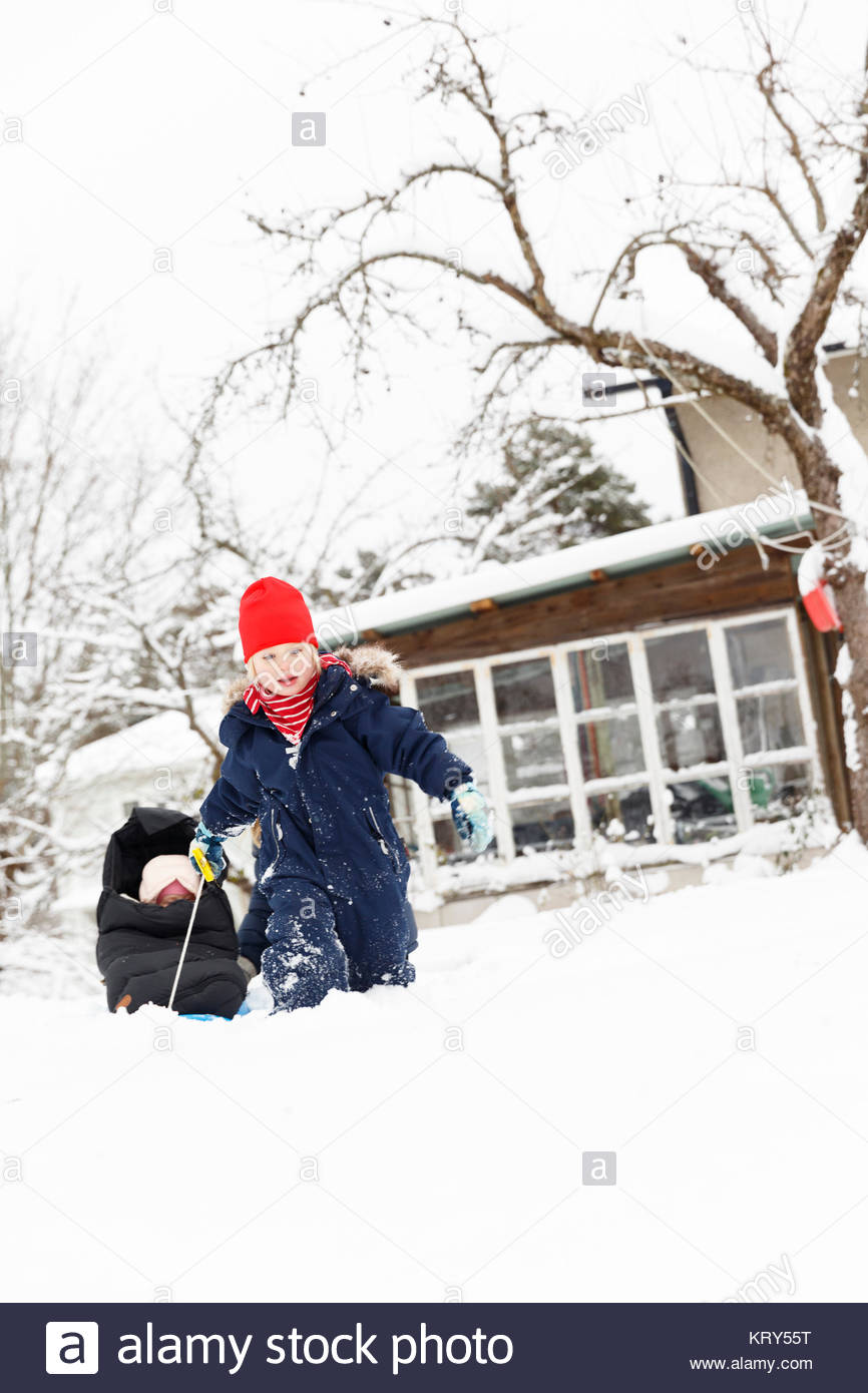 Boy pulling his sister in a sled - Stock Image