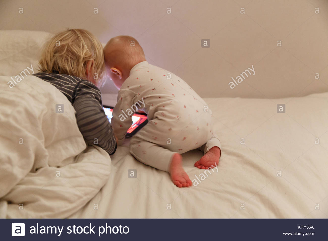 Children using a tablet in bed - Stock Image