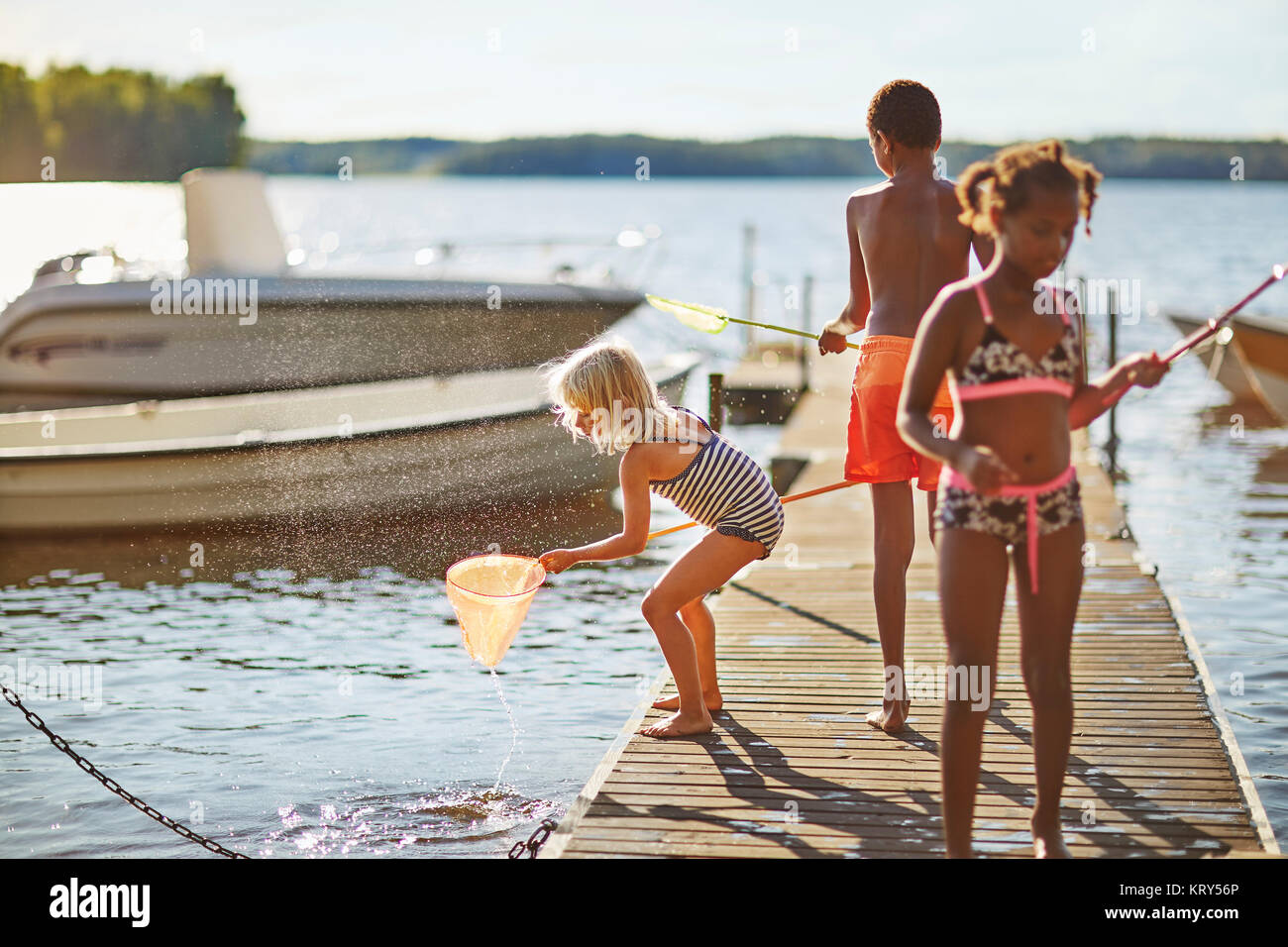 Children fishing on a pier - Stock Image