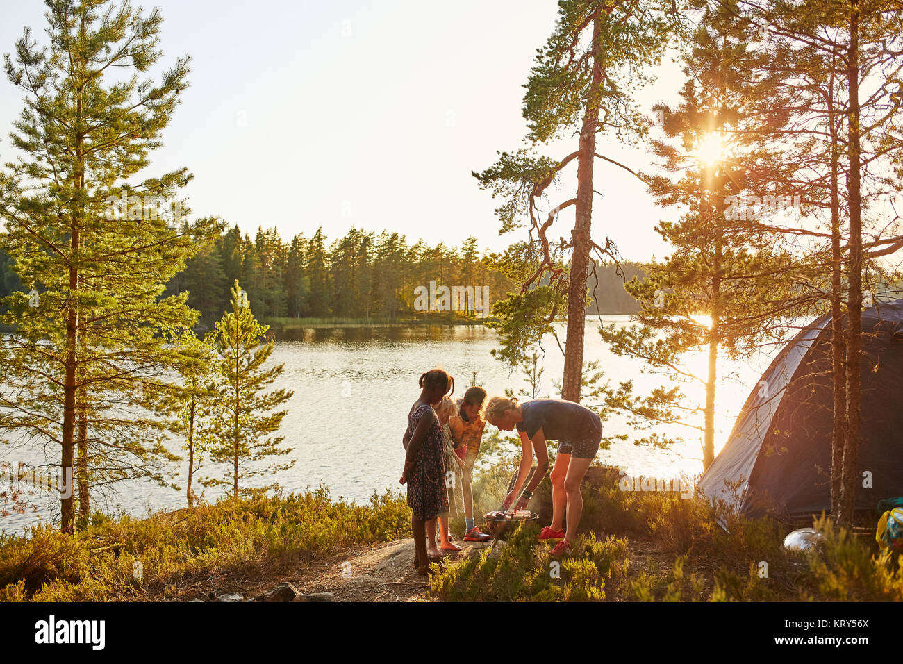 Family camping by a river - Stock Image
