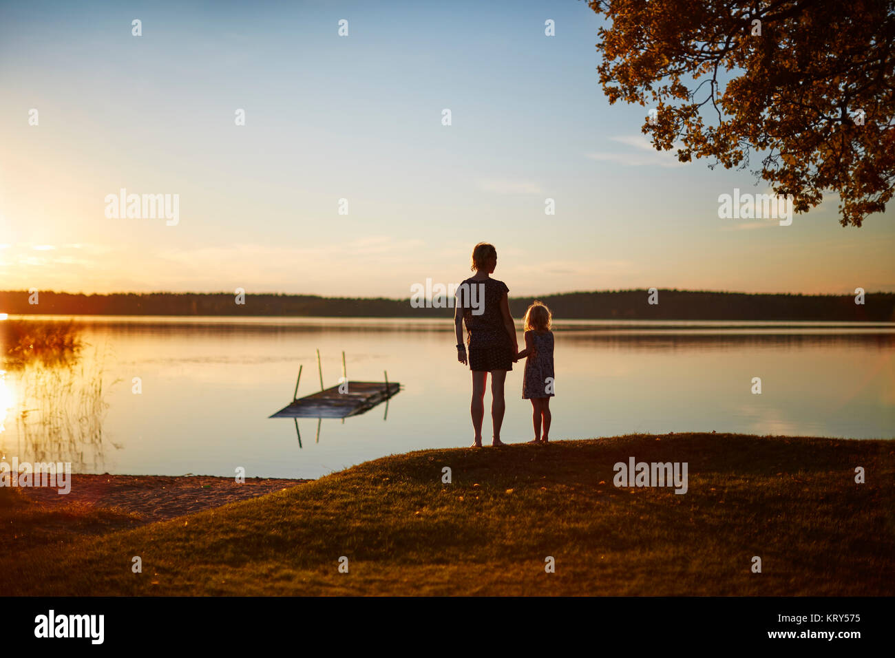 Mother and daughter by lake at sunset - Stock Image
