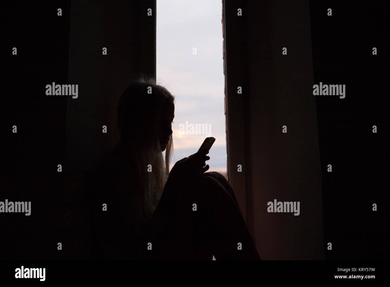 Silhouette of girl holding smart phone - Stock Image