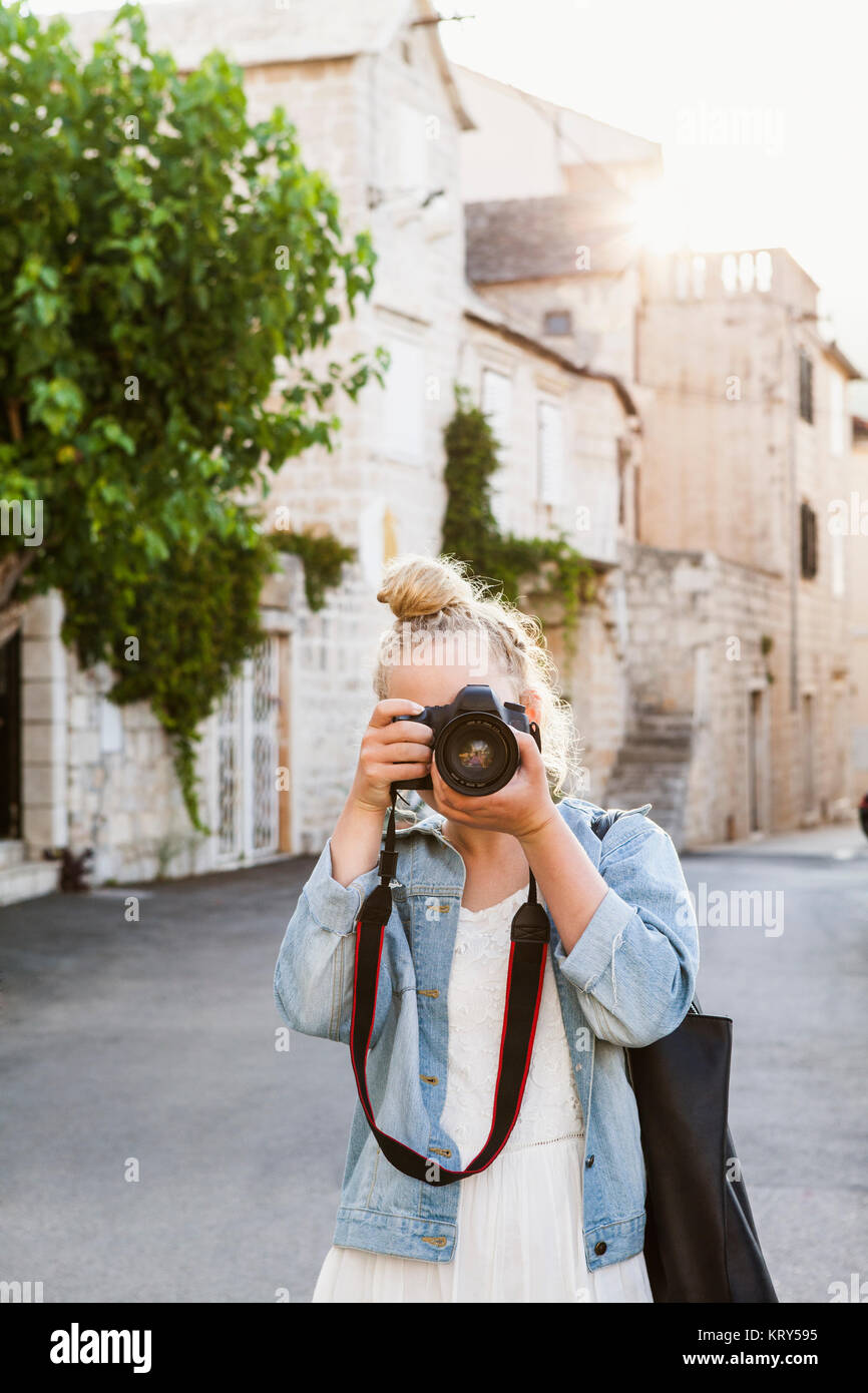 A young woman taking photos - Stock Image