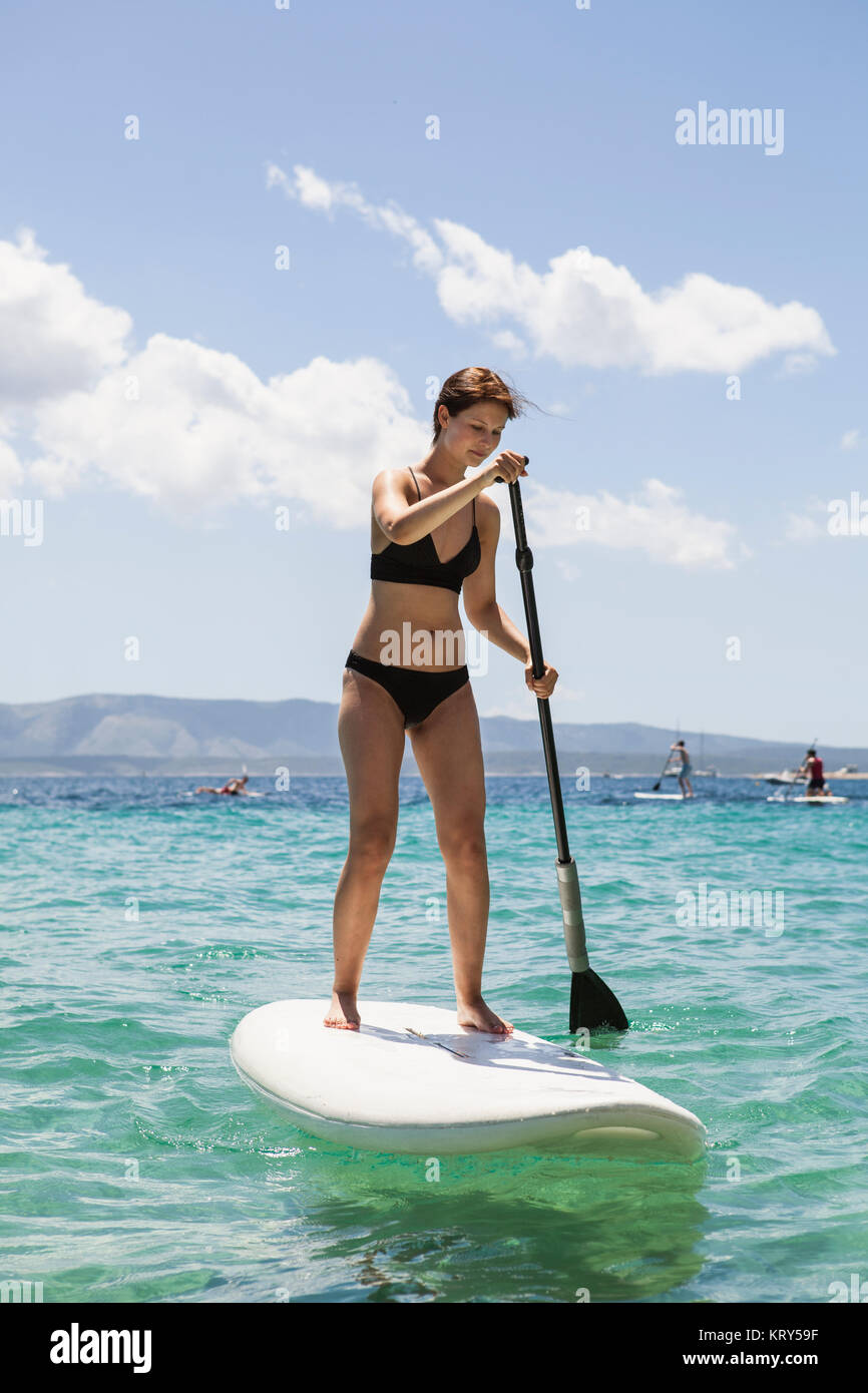 A woman paddle boarding in Croatia - Stock Image