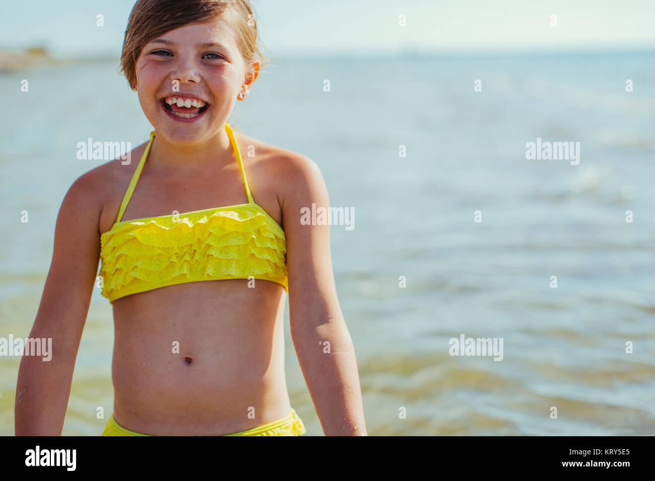 A smiling girl beside the sea - Stock Image