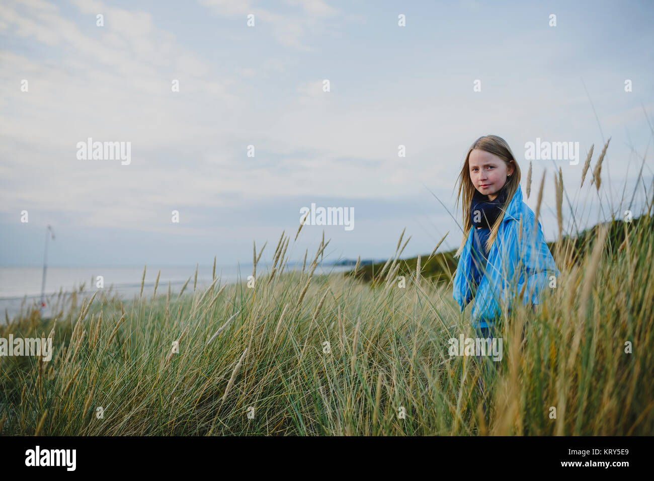 A young girl standing in long grass - Stock Image