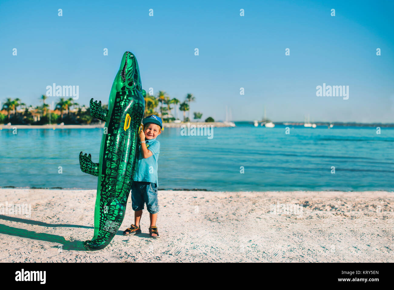 A young boy at the beach with an inflatable crocodile - Stock Image