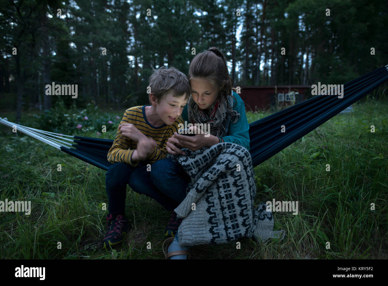 a boy and a girl in a hammock looking at a cell phone - Stock Image