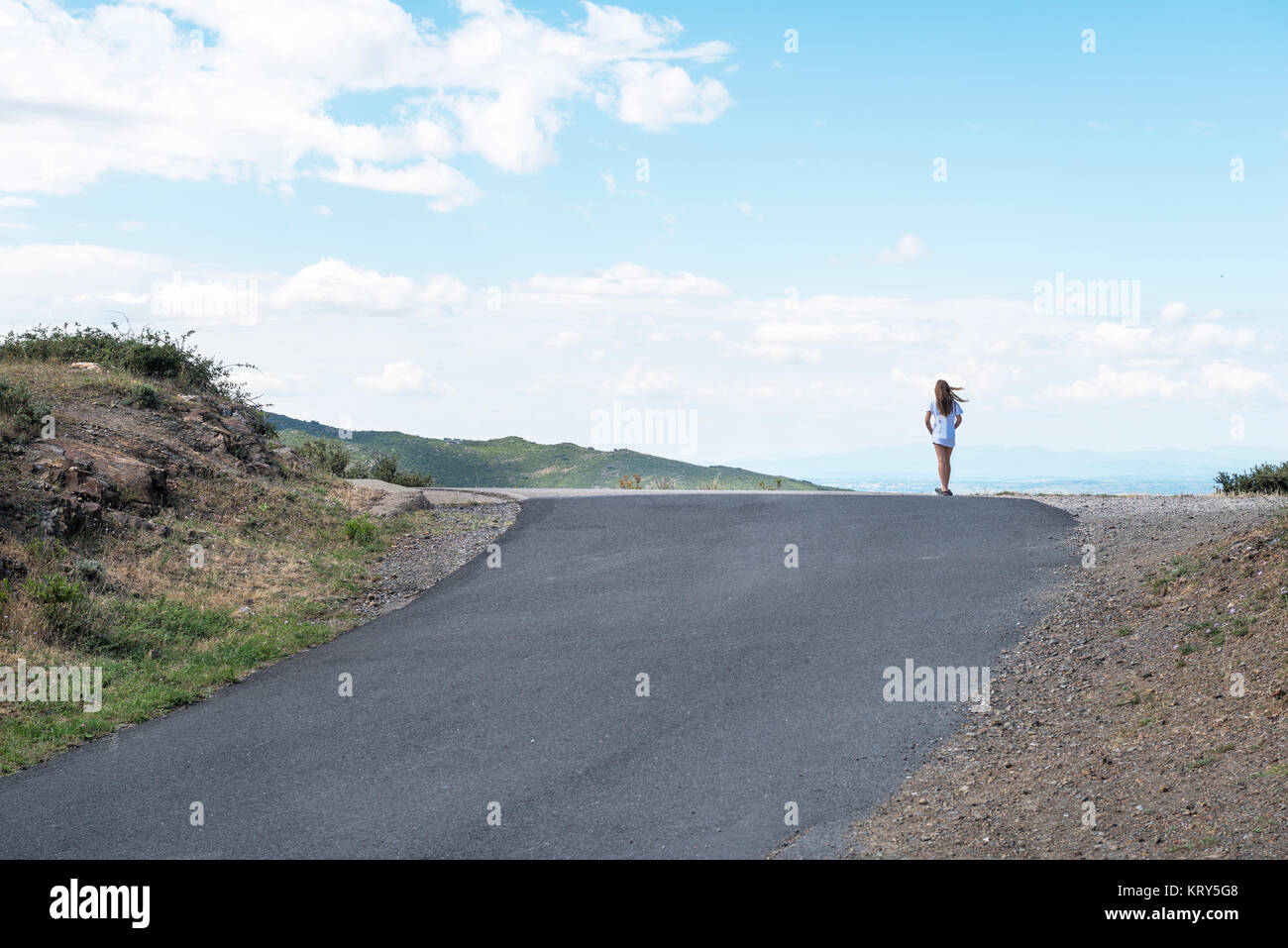a girl standing on the crest of a rural road - Stock Image