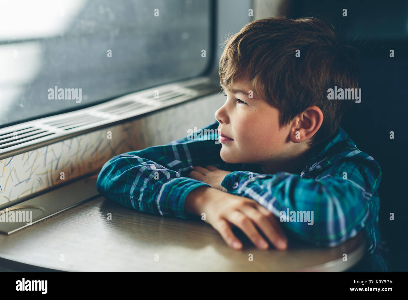 A young boy travelling on a train - Stock Image