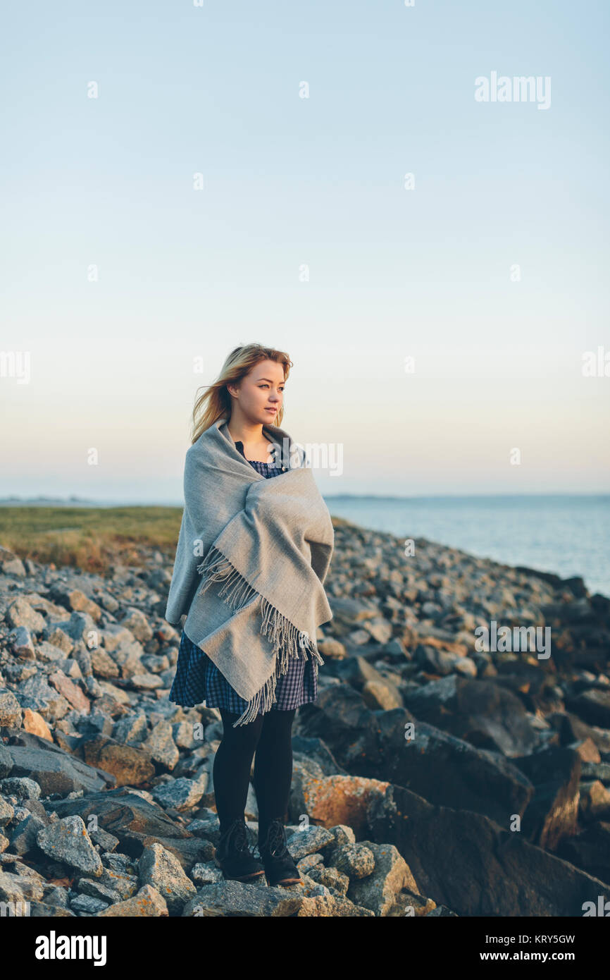 A young woman wrapped in a shawl looking out to sea - Stock Image