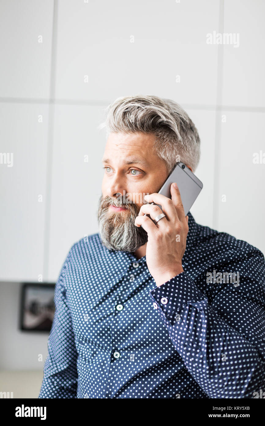 A man in a spotted shirt talking on a cell phone - Stock Image