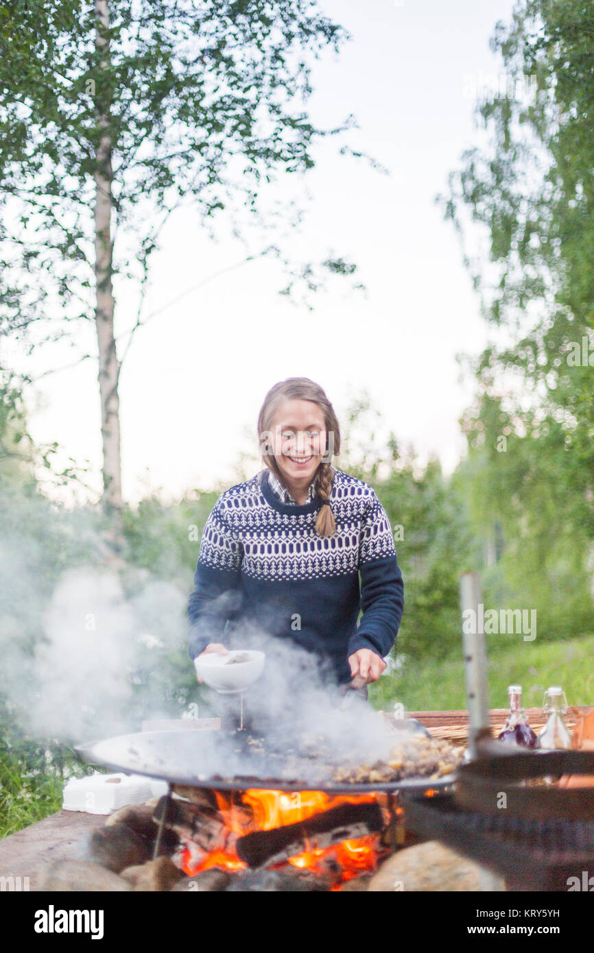 A woman cooking on a fire pit - Stock Image