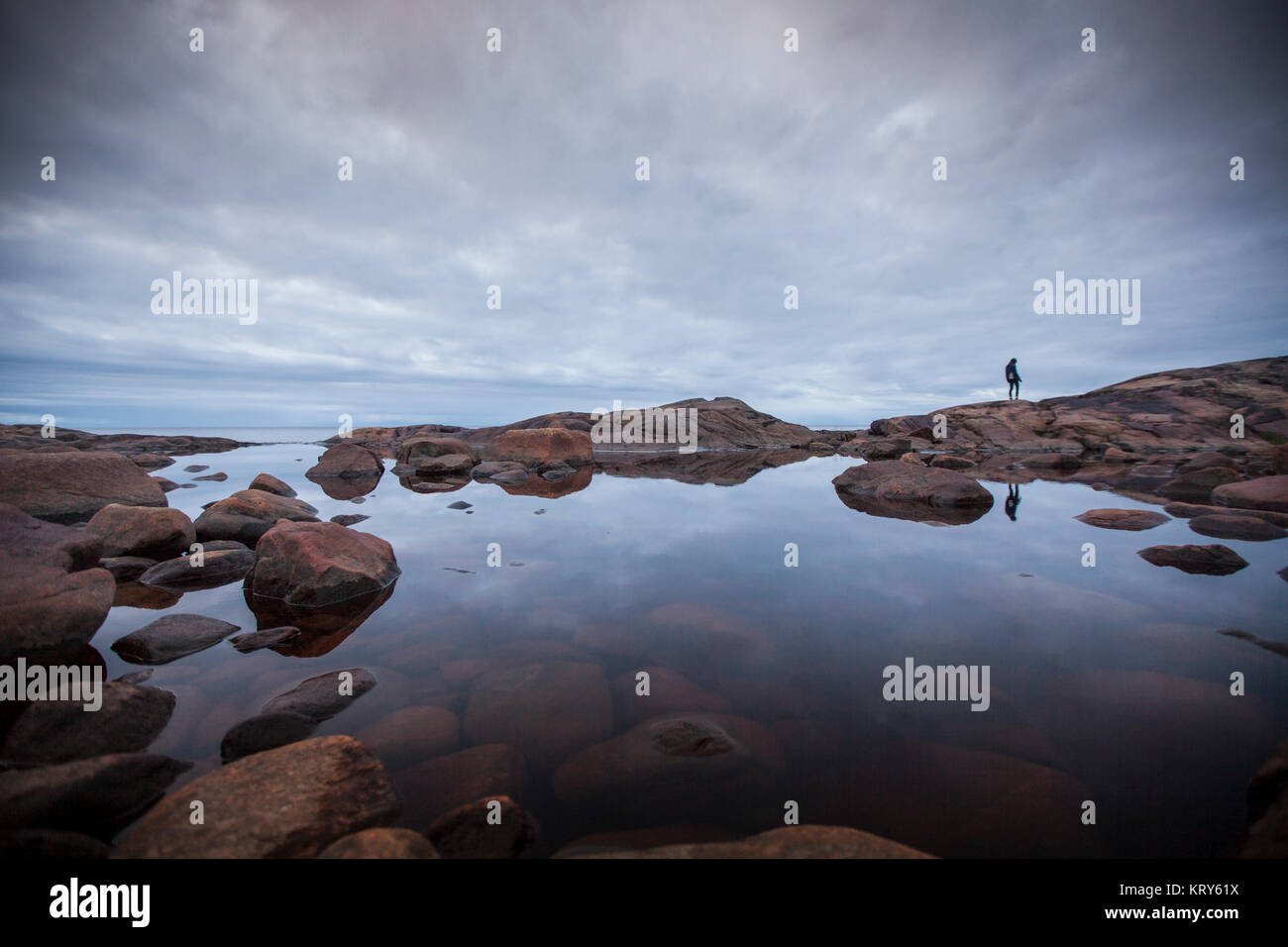 Woman standing by a rock pool in Vasterbotten, Sweden - Stock Image