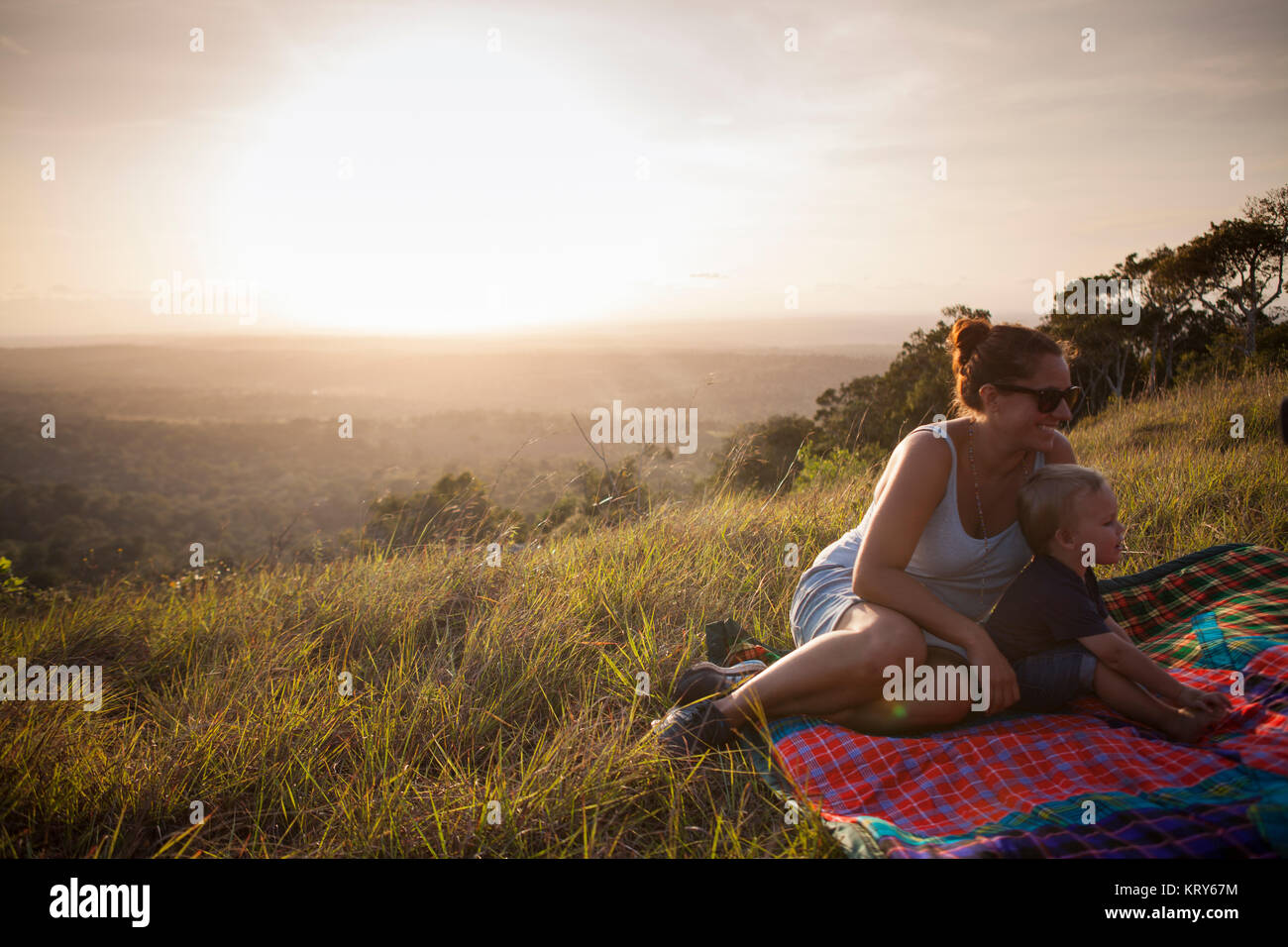 Mother and son sitting in a field in Kenya - Stock Image