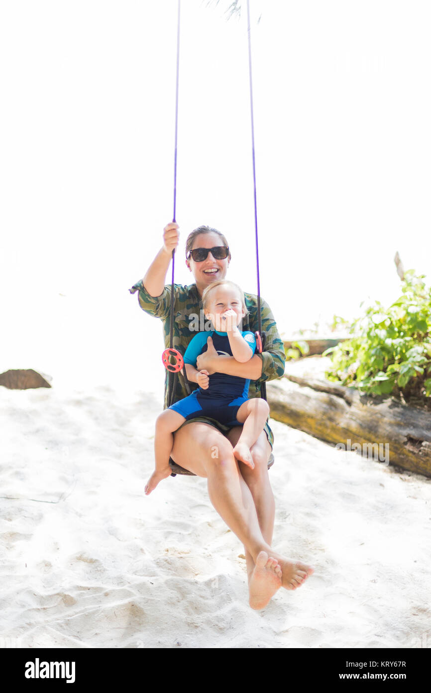 Woman holding son on swing - Stock Image