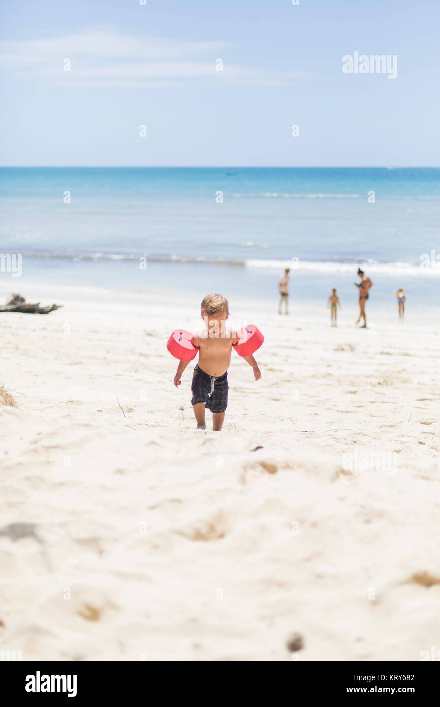 Toddler with water wings on Diani Beach in Kenya - Stock Image