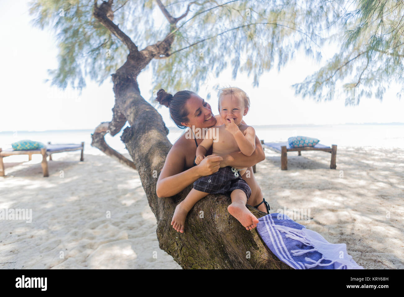 Toddler and his mother sitting on a tree at Diani Beach, Kenya - Stock Image