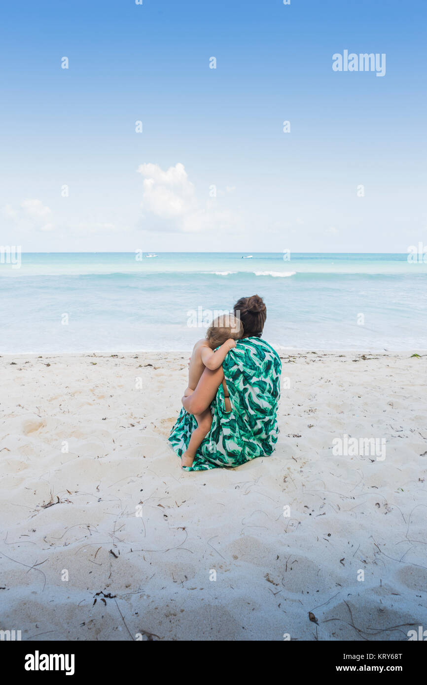 Mother and son sitting on beach in Kenya - Stock Image