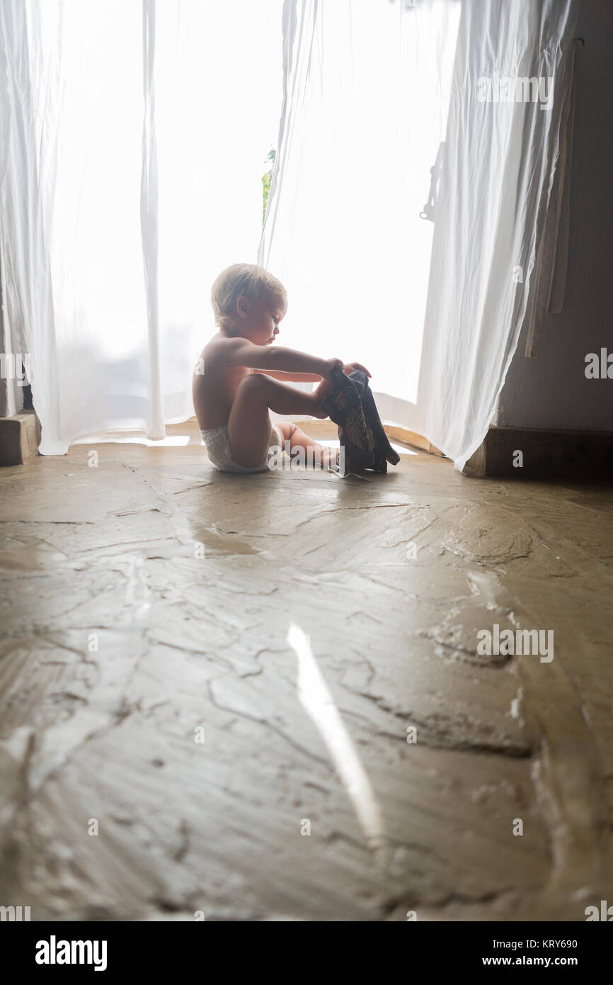 Toddler dressing himself in Kenya - Stock Image