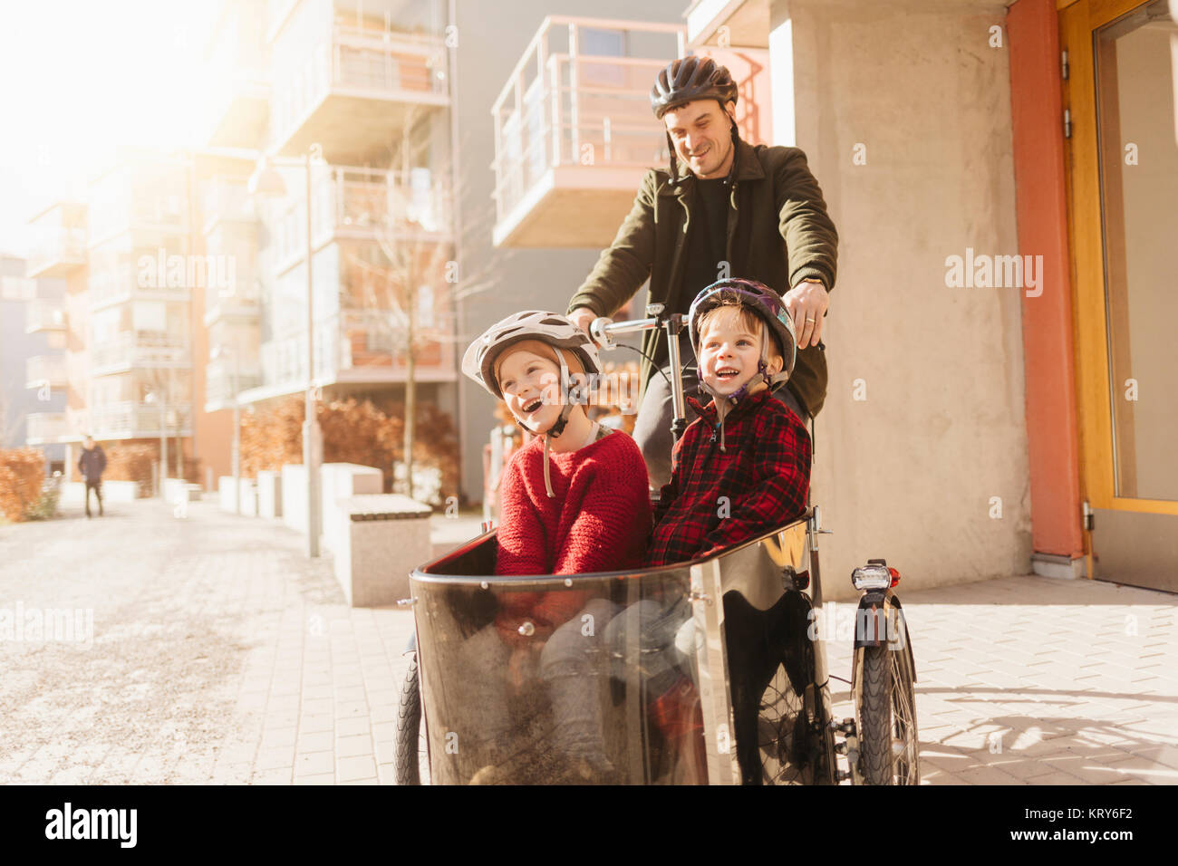 Man cycling with his sons in Stockholm - Stock Image