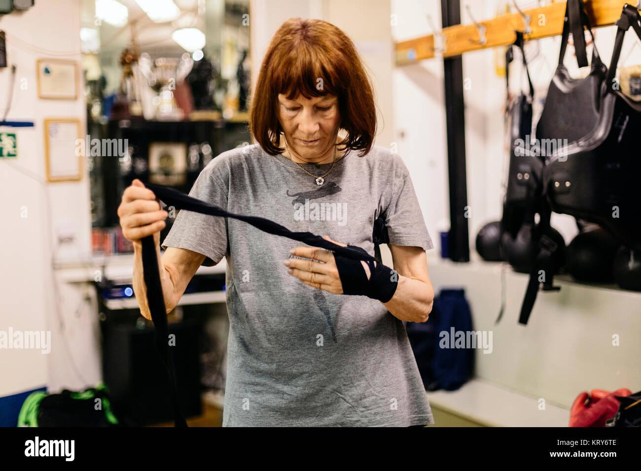 Senior woman preparing for boxing training - Stock Image