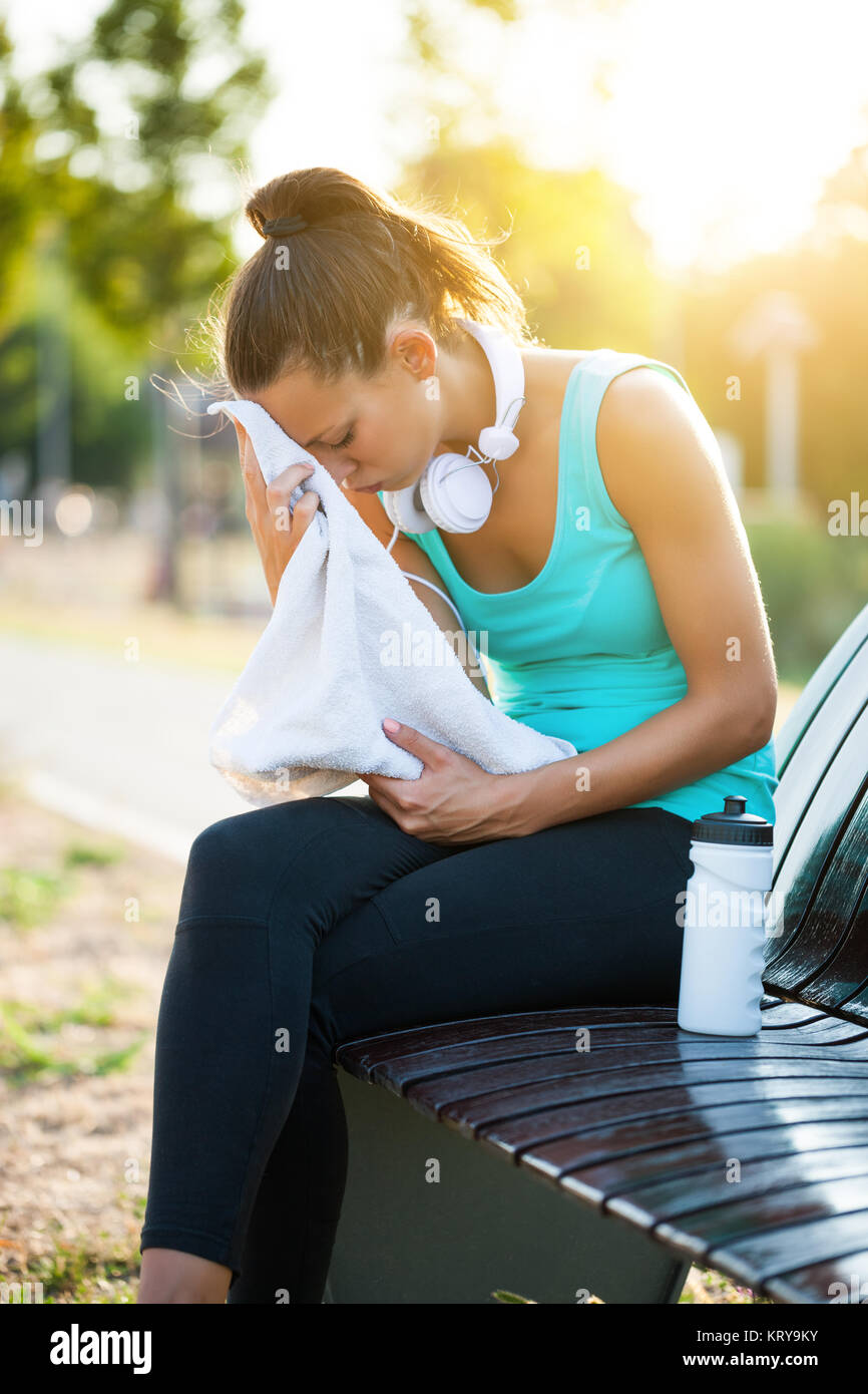 Young woman is relaxing after jogging on sunny day. - Stock Image
