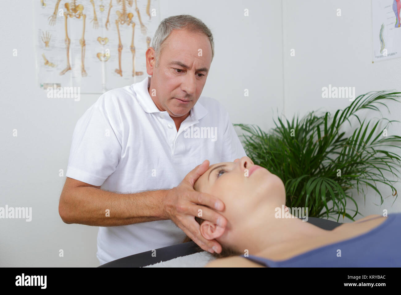 physiotherapist massages holding male clients head - Stock Image
