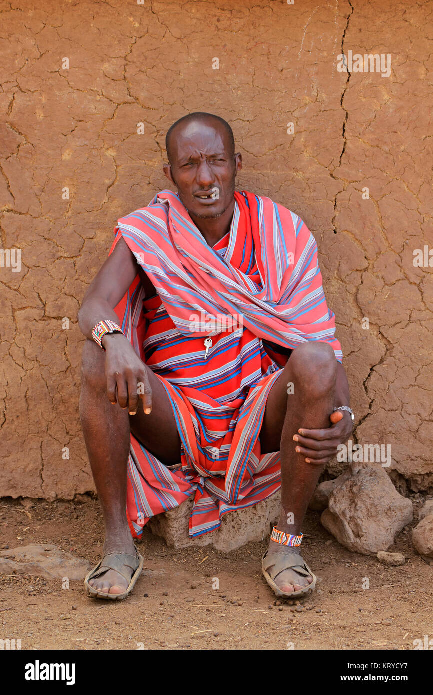 AMBOSELI, KENYA - AUGUST 31, 2013:Unidentified Masai man with traditional colorful garment sitting in front of his - Stock Image