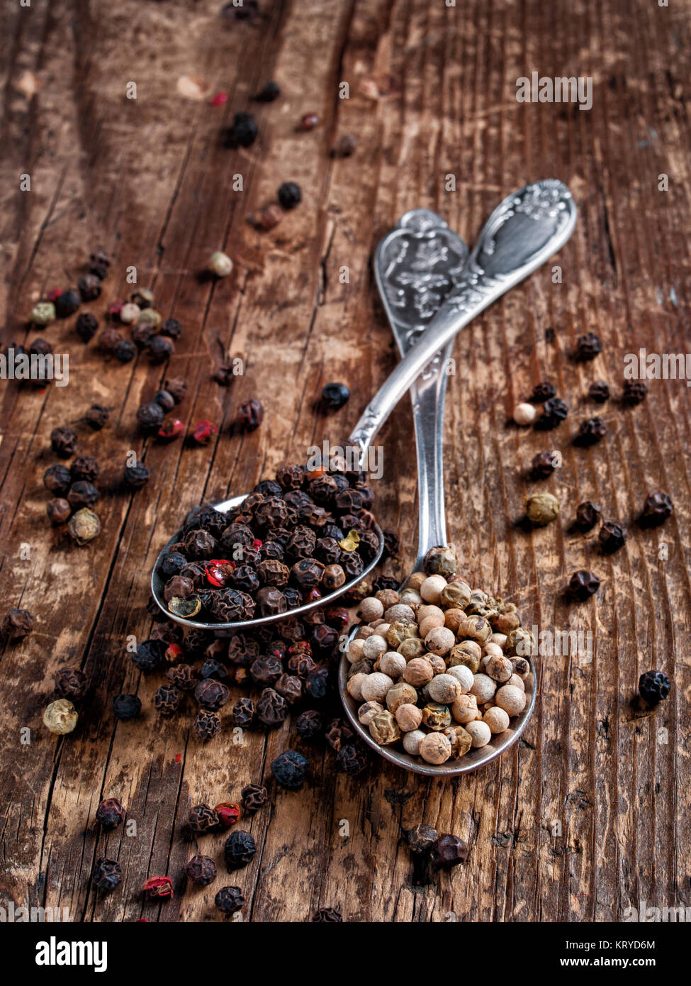Spice pepper peas dry black and white fragrant, fragrant, dry for cooking poured in two spoons lies on a wooden - Stock Image
