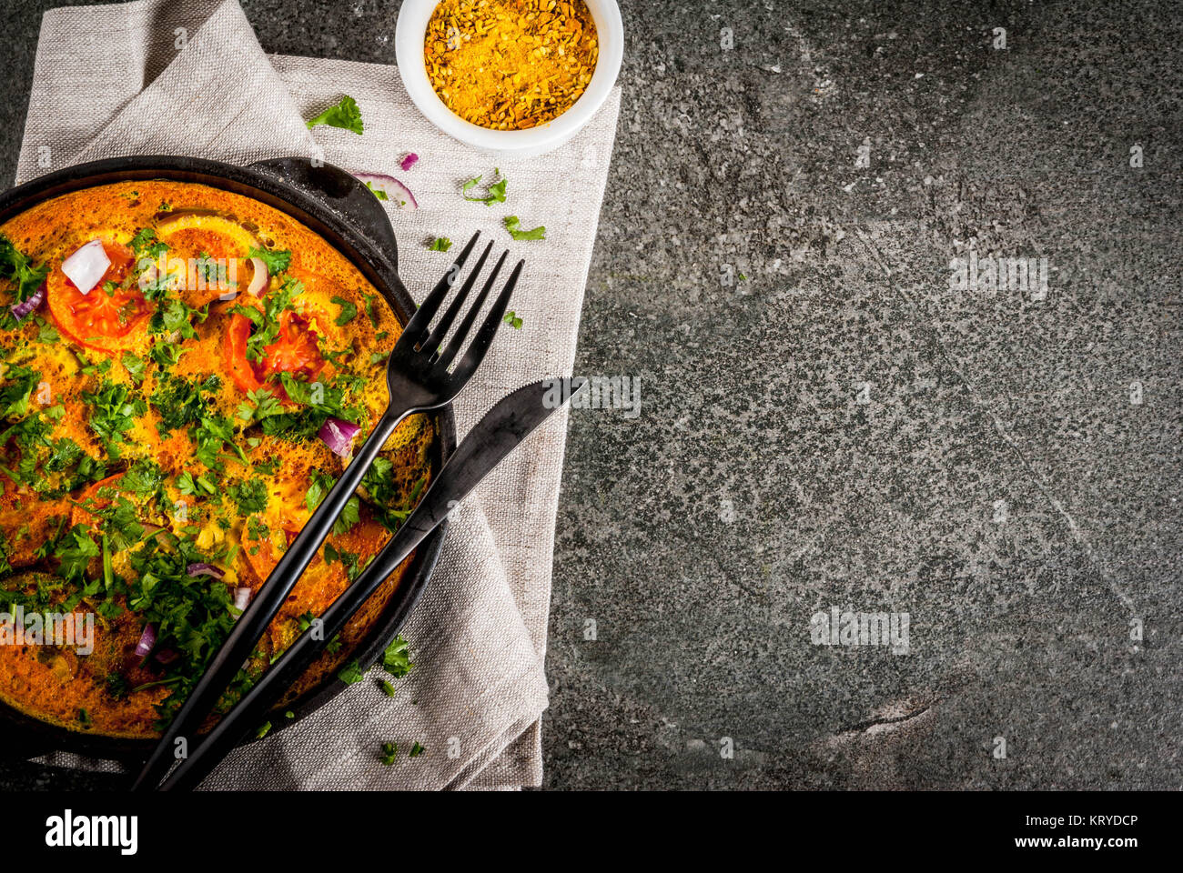 Indian food recipes, Masala Omelette with fresh vegetables - tomato, hot chili pepper, parsley, dark stone background, Stock Photo