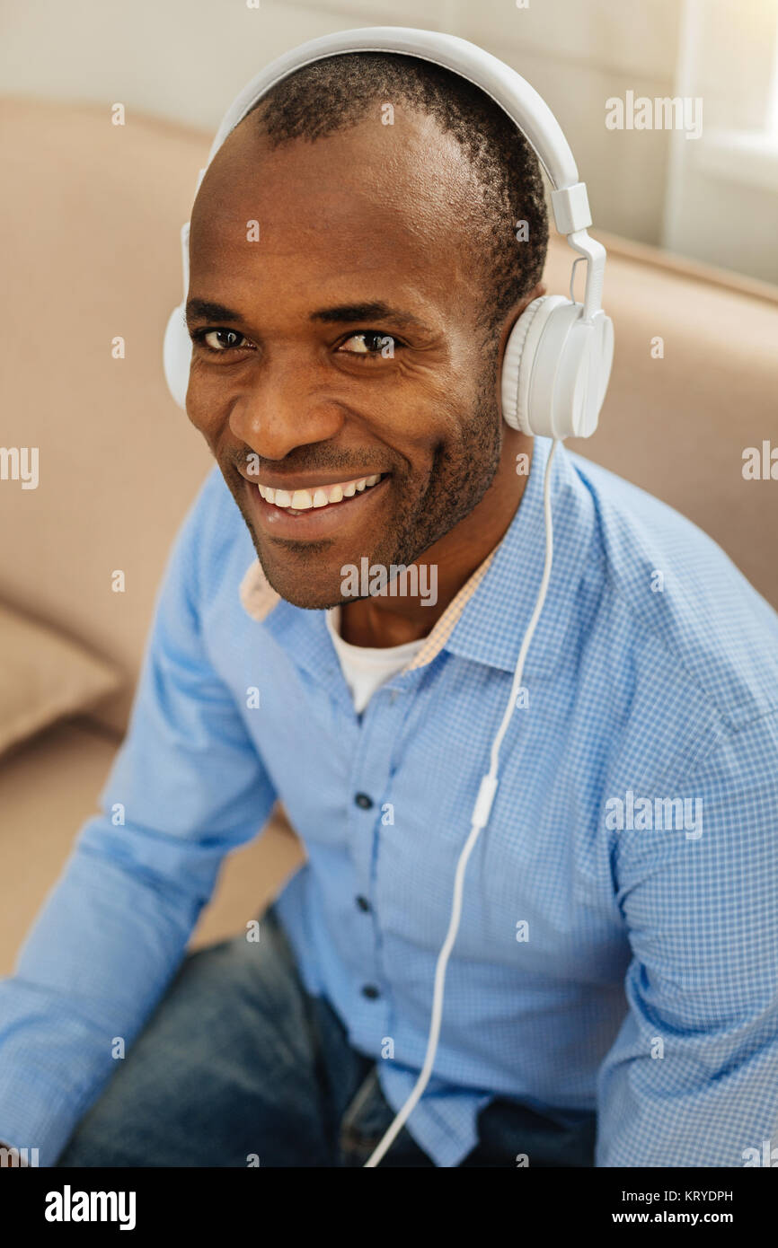 Beaming man listening to music - Stock Image